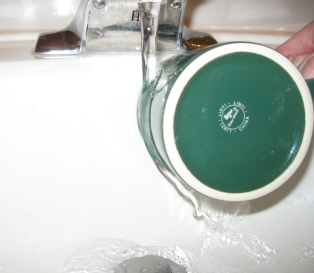 A stream of water from a faucet being diverted to side after it touch a drinking cup